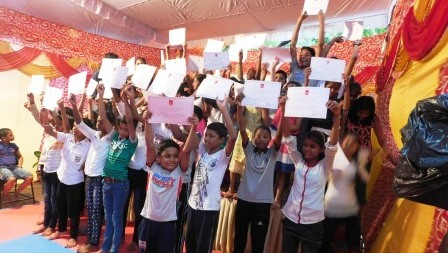 Children waving their certificates of participation
